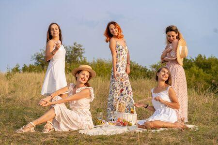 The company of stylish happy female friends having fun on outdoor retro style picnic party. Foto de archivo