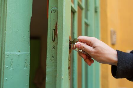 Unlocks the old green wooden entrance door.