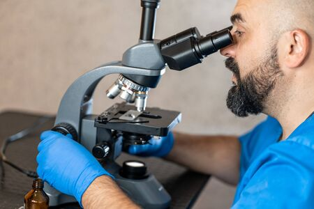 Male laboratory assistant examining biomaterial samples in a microscope