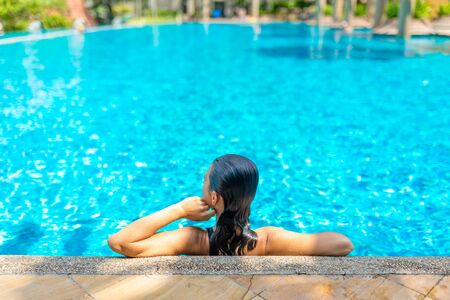 Young sexy slim woman relaxing in tropical swimming pool with crystal blue water in hot summer day. Archivio Fotografico - 138035405