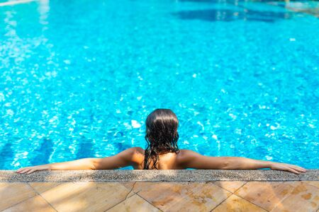 Young sexy slim woman relaxing in tropical swimming pool with crystal blue water in hot summer day. Archivio Fotografico - 138035408