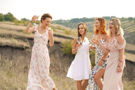 The company of gorgeous female friends having fun and enjoys a summer green hlls picnic, dancing and drink alcohol. People concept