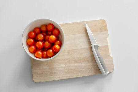 A bowl of cherry tomatoes on a cutting board. Cooking healthy and tasty food.