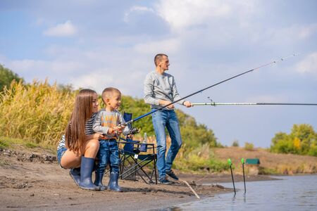 A happy family spends time together they teach their son to fish Banco de Imagens