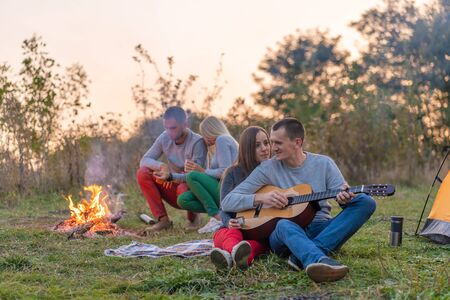 Group of happy friends with guitar, having fun outdoor, near bonfire and tourist tent. Camping fun happy family. Banco de Imagens - 138420555