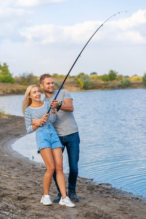 Happy young couple fishing by lakeside. Banco de Imagens