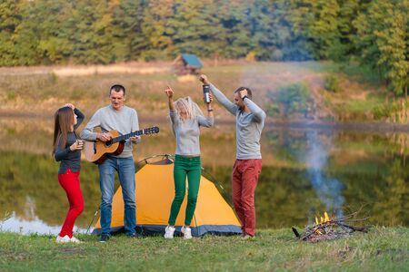 Group of happy friends with guitar, having fun outdoor, dancing and jumping near the lake in the park background the Beautiful sky. Camping fun. Banco de Imagens - 138420743