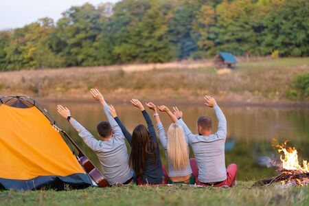 Shoot from back. A group of happy friends camping at riverside, dancing hold hands up and enjoy view. Holidays fun.