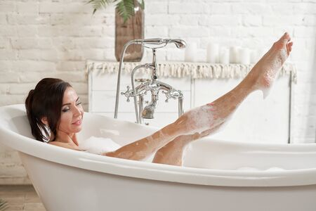 A gorgeous woman is enjoying herself in a white bathtub, in a bright room with a large window