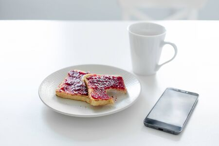 Breakfast is on the table. A cup of coffee and toast with cherry jam next to the phone.