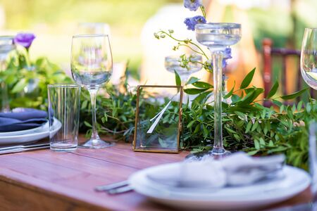 Preparing for an open-air party. Decorated with fresh flowers served tables. Table number. Decoration Details.