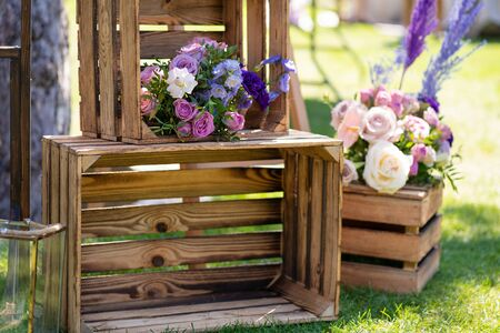 Decorative element from wooden boxes and fresh flowers. Details Party Decoration.