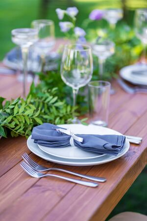 Beautifully decorated wooden table in a summer open-air cafe. Green branch and fresh flowers table decoration.