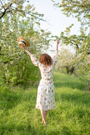 Young attractive woman with curly hair walking in a green flowered garden. Spring romantic mood.