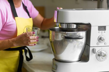 Woman professional pastry chef preparing a dessert. Adds ingredients and mixes the dough in a mixer.