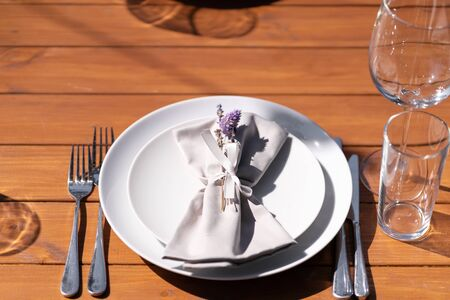 Beautifully served wooden table without a tablecloth. White plates on a wooden table.