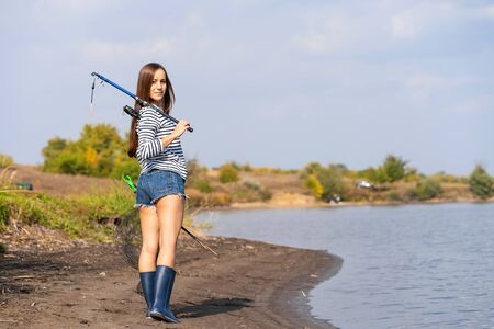 A beautiful young girl goes fishing. A girl with a fishing rod and a cage in hand is walking along the lake.