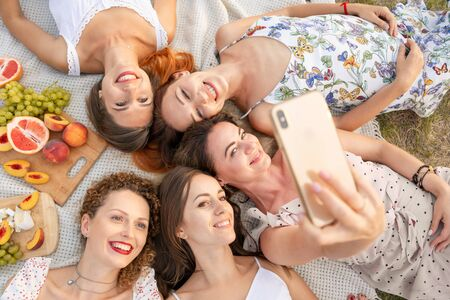 View from above. The company of beautiful girlfriends have fun and enjoy a picnic outdoors and take pictures on a mobile phone.