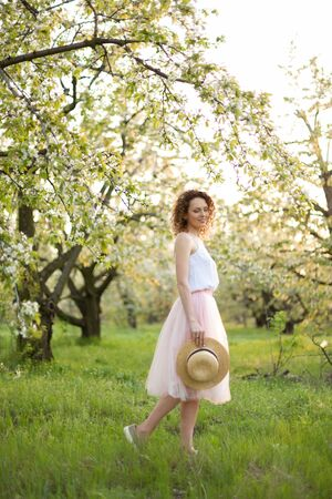 Young attractive woman with curly hair walking in a green flowered garden. Spring mood. Archivio Fotografico