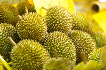Fresh stinky durian fruit in a window display of a street Asian store.