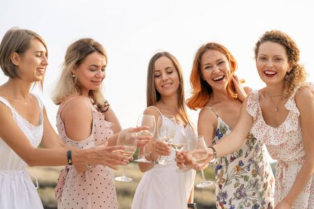 W towarzystwie koleżanek urządza się letni piknik i wznosi kieliszki z winem.