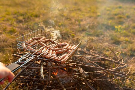 Sausages in the grill at the stake. A picnic in nature at sunset. Taste of summer.