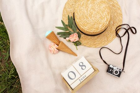 Accessories of a romantic girl traveler. Wicker hat and retro camera.