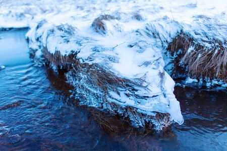 Incredible winter landscape of Iceland. In winter, a source of hot water flows in the mountains. Imagens