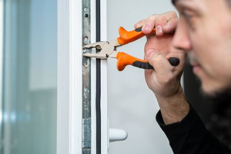 Professional master for repair and installation of windows, sets up a window opening system in winter mode.