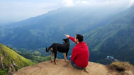 A guy with a dog enjoying the mountain scenery on the edge of a cliff.