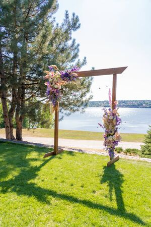 A beautiful venue for an open-air wedding ceremony. Wedding arch and rows of guest chairs on a green lawn overlooking the river. Standard-Bild - 140174358