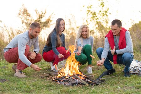 travel, tourism, hike, picnic and people concept - group of happy friends frying sausages on campfire.