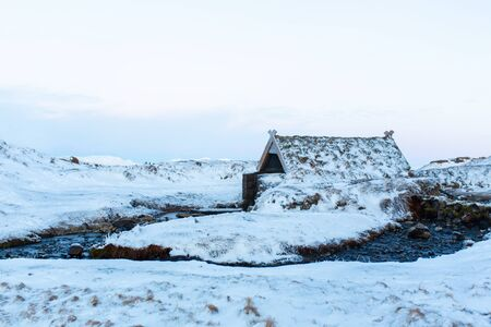 An old bathhouse with a hot spring in the mountains of Iceland. Iceland winter landscape.
