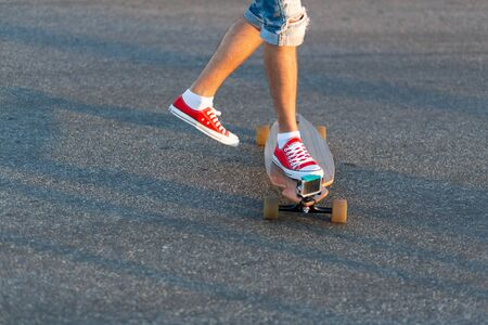 Man in red sneakers jumps on skateboard for ride.
