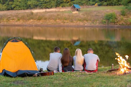 A group of friends is enjoying view, camping with bonfire on riverside. Standard-Bild - 140175087
