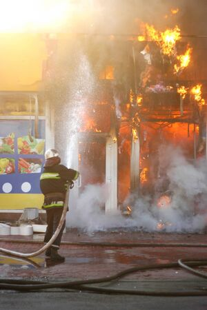 Firefighter extinguishes a fire in a burning building with water from a hose. Hazardous work fireman. Editorial
