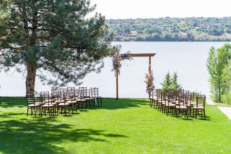 A beautiful venue for an open-air wedding ceremony. Wedding arch and rows of guest chairs on a green lawn overlooking the river.