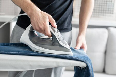 A guy ironing clothes before going outside.