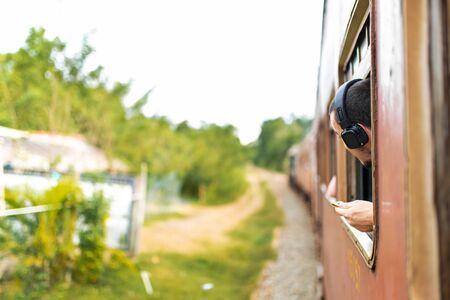 Train ride in Sri Lanka. The man in the headphones looks out the window. Banco de Imagens