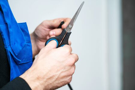 Professional window repair and installation technician, cuts sealing rubber for installation in a pvc window. Banque d'images