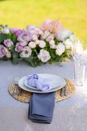 Decorative decoration of the festive table. Glass vases and fresh flowers. Decoration of holidays in the open air.