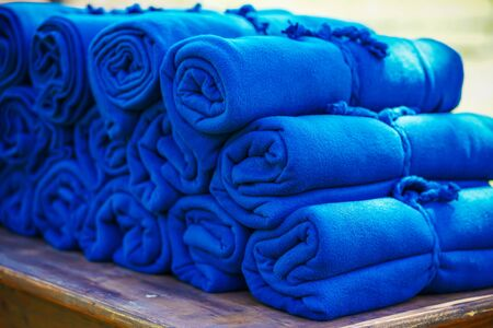 A set of warm blue rugs at an open-air party, in case guests feel cold in the evening. Stock fotó