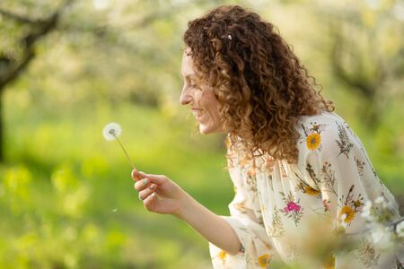 Pretty girl blowing dandelion in summer park. Green grass beautiful nature. Pure emotion Imagens