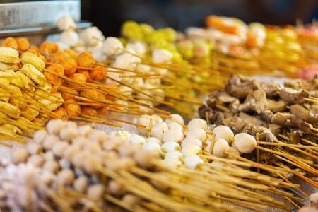 Traditional fried chinese food on sticks at night street vendor market. Banco de Imagens