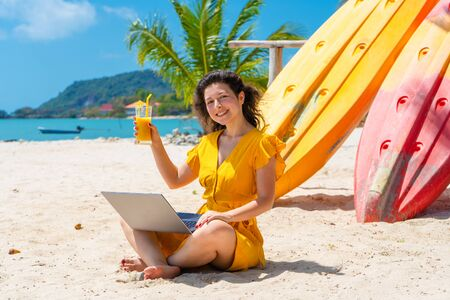 Girl in a yellow dress on a tropical sandy beach works on a laptop near kayaks and drinks fresh mango. Remote work, successful freelance. Works on vacation