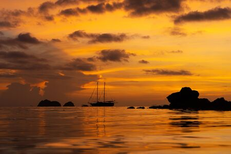 Colorful sunset on a tropical beach. Orange sunset on the ocean. Colorful sunset in the tropics. In the water is a sailing ship. Silhouetted sailboat with masts. Archivio Fotografico