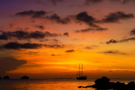 Colorful sunset on a tropical beach. Orange sunset on the ocean. Colorful sunset in the tropics. In the water is a sailing ship. Silhouetted sailboat with masts.