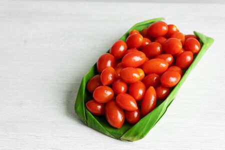 Cherry tomatoes in a banana leaf. Eco friendly packaging.