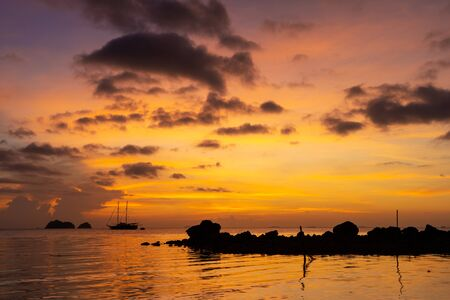 Colorful sunset on a tropical beach. Orange sunset on the ocean. Colorful sunset in the tropics. In the water is a sailing ship. Silhouetted sailboat with masts. Stock fotó