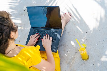 Girl in a yellow dress on a tropical sandy beach works on a laptop and drinks fresh mango. Remote work, successful freelance. Works on vacation